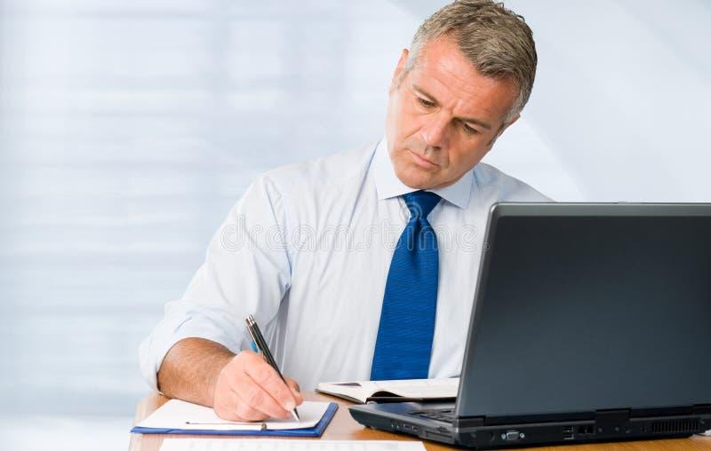 Rijpe zakenman die in bureau werkt stock foto's