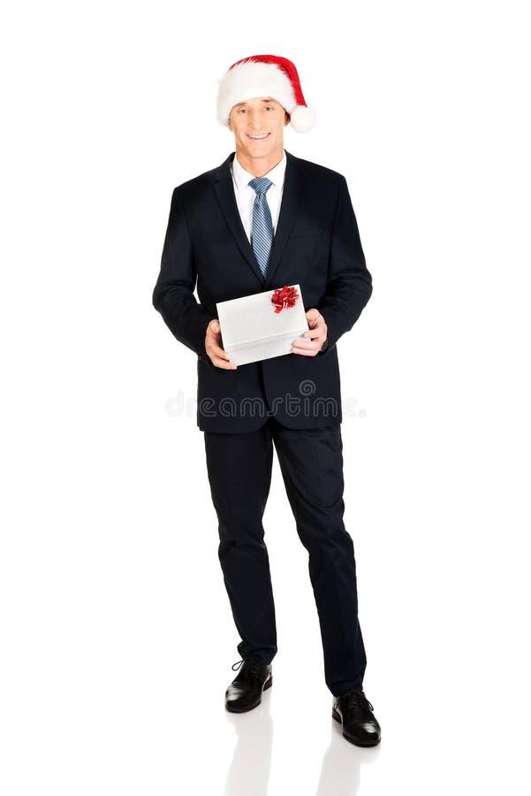 Rijpe zakenman die de holdingsgift dragen van de santahoed royalty-vrije stock foto