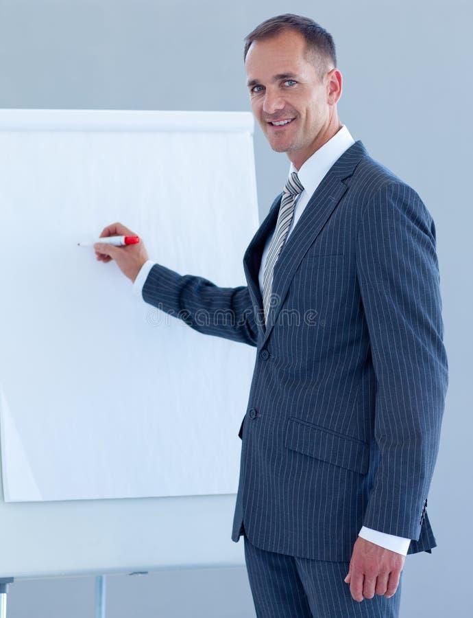 Rijpe zakenman die in een whiteboard schrijft royalty-vrije stock foto