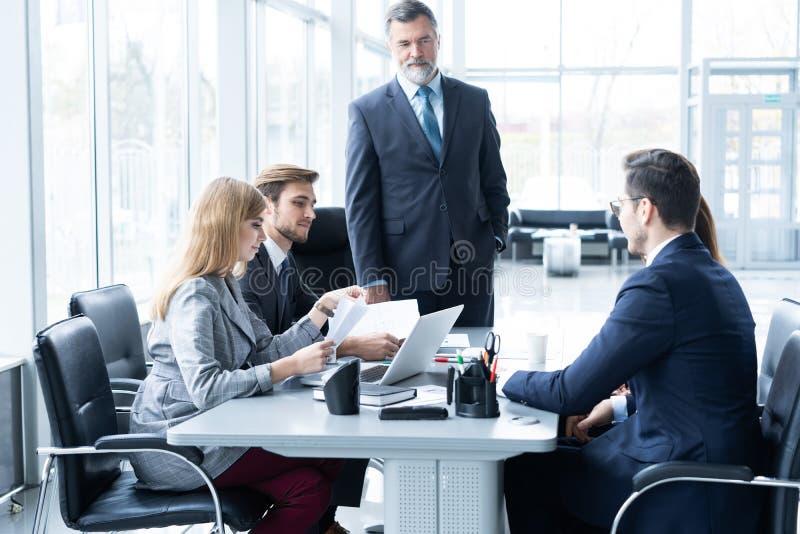 Rijpe zakenman die en zijn bedrijfsstrategie spreken verklaren aan zijn collega's op kantoor royalty-vrije stock foto's