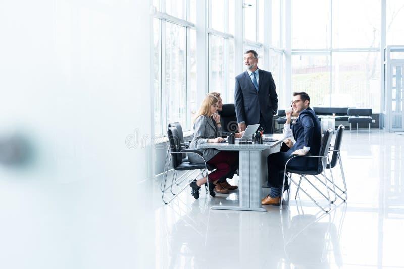 Rijpe zakenman die en zijn bedrijfsstrategie spreken verklaren aan zijn collega's op kantoor royalty-vrije stock foto