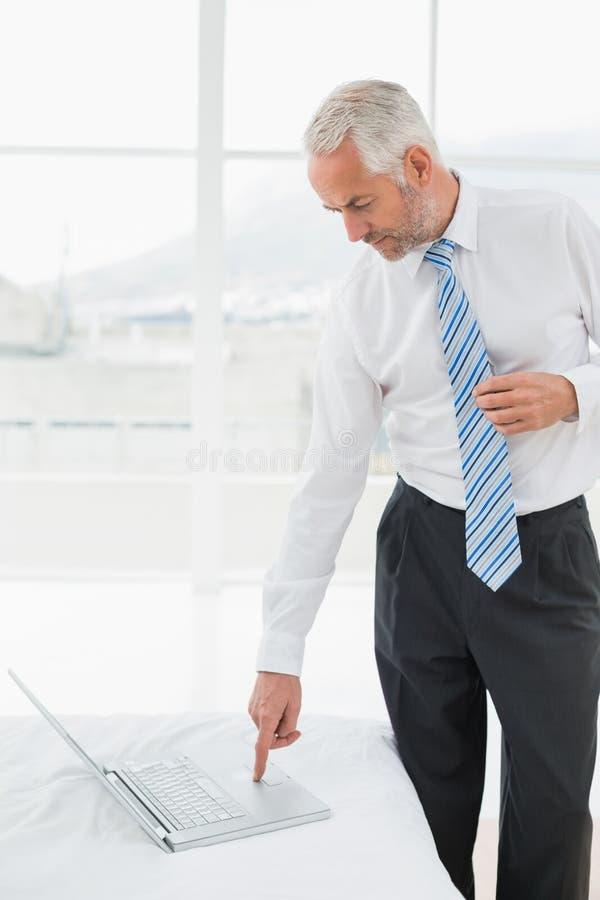 Rijpe zakenman die laptop met behulp van bij een hotelruimte stock foto's