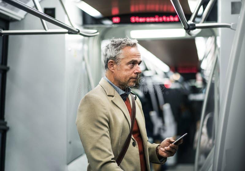 Rijpe zakenman die met smartphone door metro in stad reizen stock foto