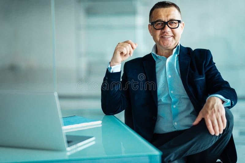 Rijpe zakenman die op administratie schrijven en met laptop in zijn modern bureau werken royalty-vrije stock foto