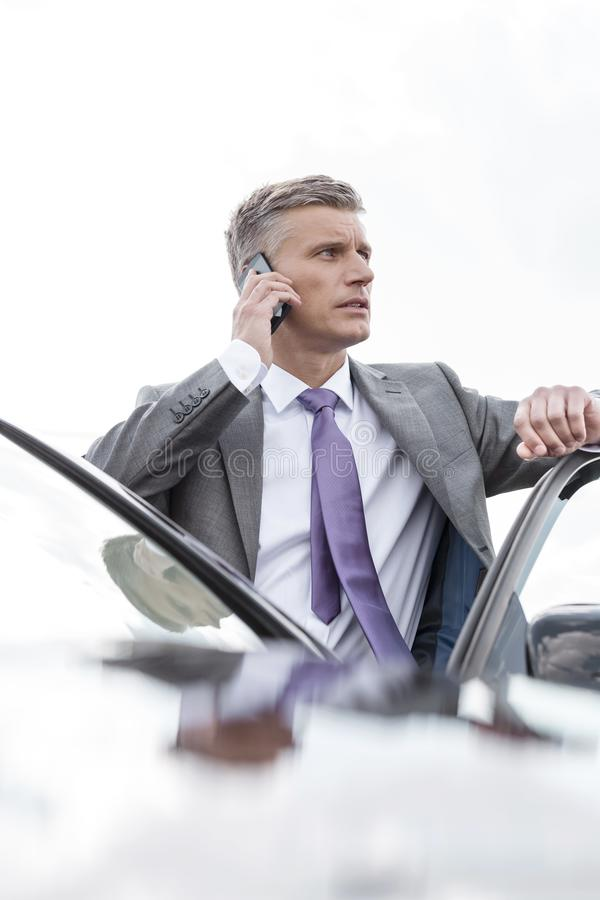 Rijpe zakenman die op mobiele telefoon spreken terwijl status buiten auto tegen hemel stock foto's