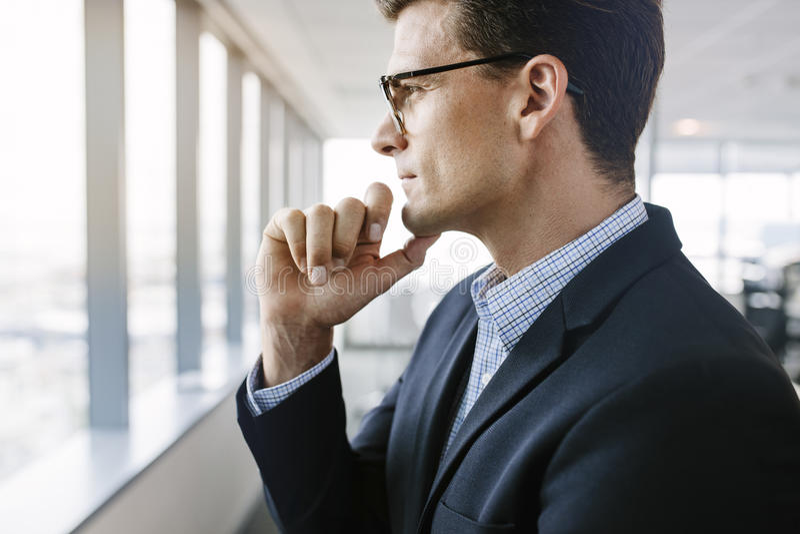 Rijpe zakenman die zich door venster en te denken bevinden stock foto's