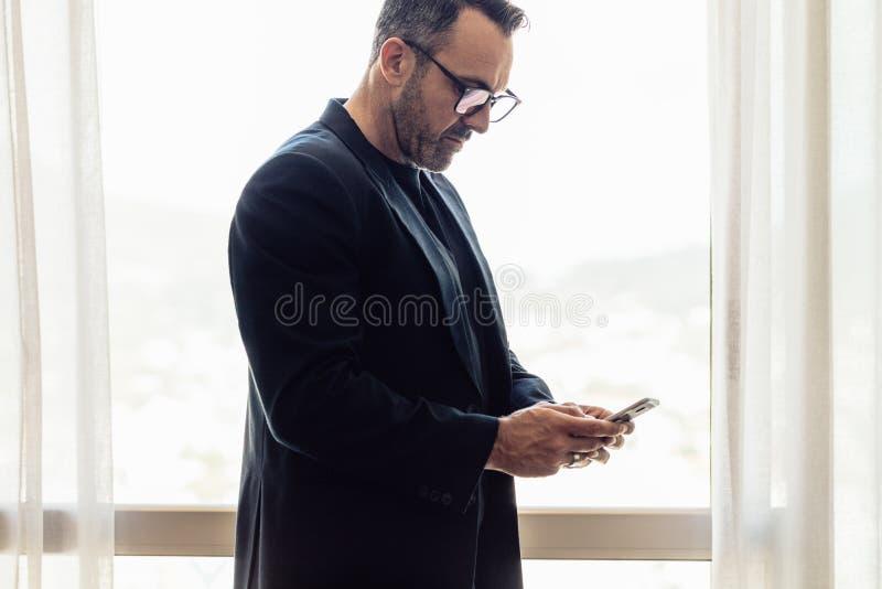 Rijpe zakenman die zich in hotelruimte bevinden die zijn celtelefoon met behulp van CEO bij zakenreis het texting op mobiele tele stock afbeeldingen