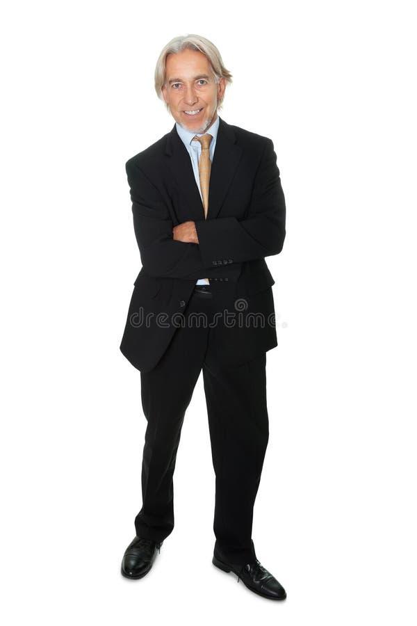 Rijpe zakenman die zich op witte achtergrond bevindt royalty-vrije stock afbeeldingen