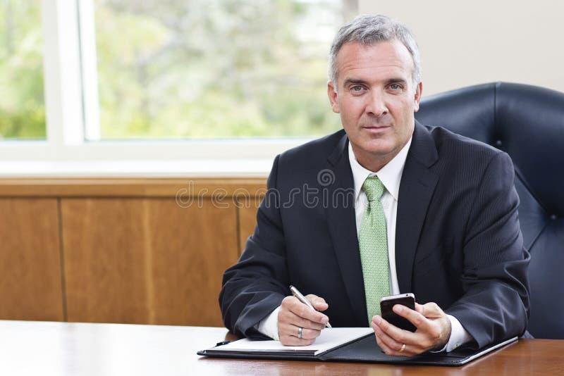 Rijpe Zakenman die in zijn bureau werken stock afbeelding