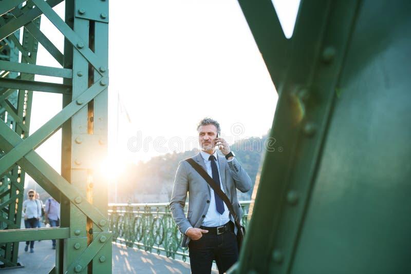 Rijpe zakenman met een smartphone in een stad stock fotografie