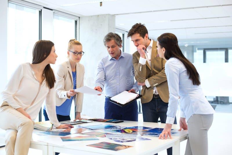 Rijpe zakenman met team die aan nieuw project op kantoor werken stock foto's