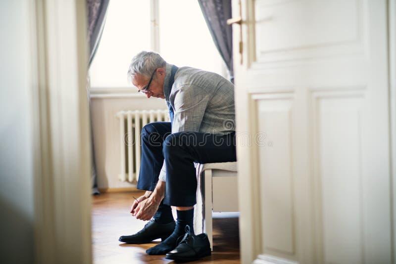 Rijpe zakenman op een zakenreiszitting in een hotelruimte, bindende schoenveters stock afbeelding