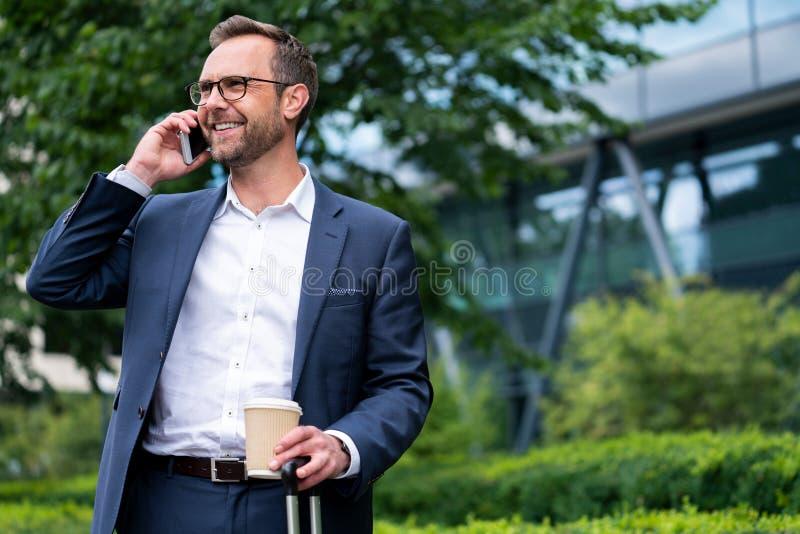 Rijpe Zakenman Taking Phone Call op Mobiele Telefoon die zich buiten de Bureaubouw bevinden stock foto