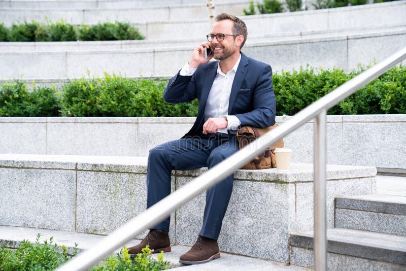 Rijpe Zakenman Taking Phone Call op Mobiele Zitting bij de Buitenbureaubouw stock afbeelding