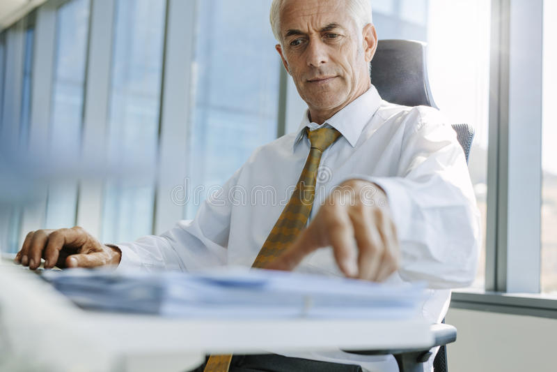 Rijpe zakenmanzitting bij zijn bureau en het werken stock afbeelding
