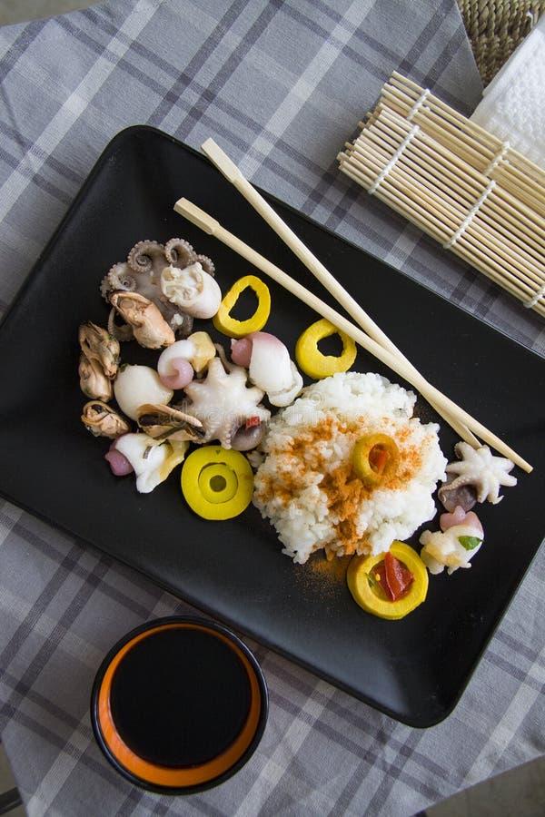 Rijst, bamboe en zeevruchten op zwarte plaat stock fotografie