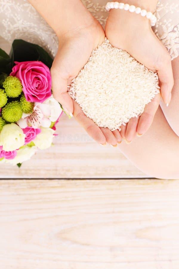 Rijst in de handen van een bruid stock afbeelding