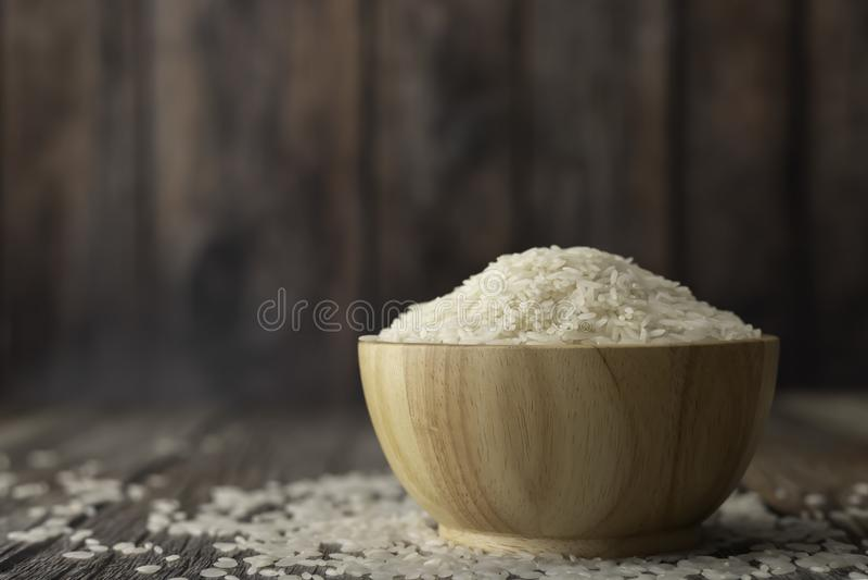 Rijst in een bruine kom op de houten lijst stock afbeeldingen