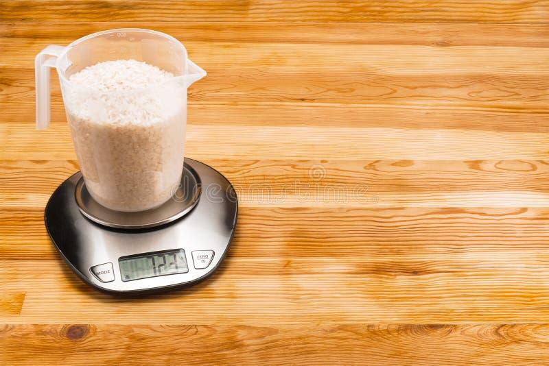 Rijst in een maatregelenkop op elektronische schaal op een houten achtergrond met exemplaarruimte stock foto's