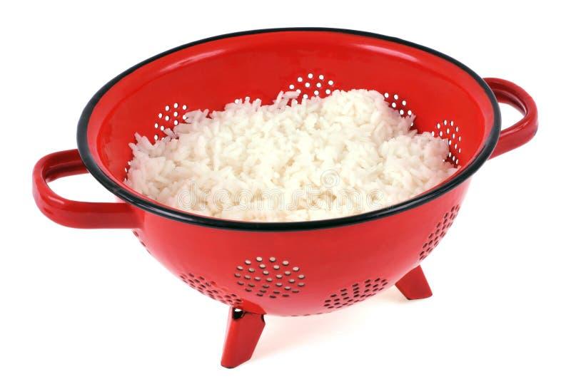 Rijst in een rood vergiet op een witte achtergrond royalty-vrije stock fotografie