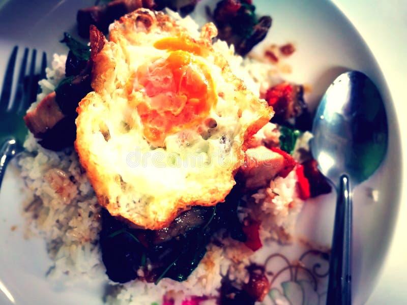 Rijst en be*wegen-gebraden knapperig varkensvlees en basilicum met de Gebraden van het de straatvoedsel van het eibovenste laagje stock afbeeldingen