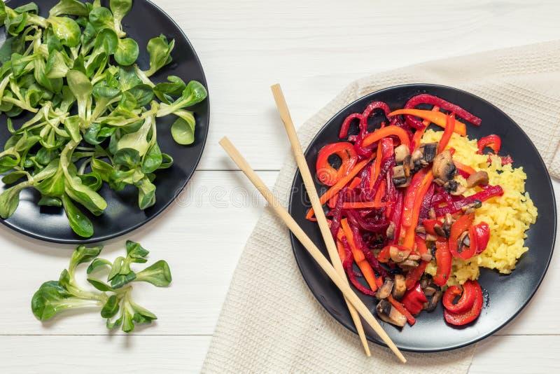 Rijst en gestoomde groenten op een zwarte plaat stock foto