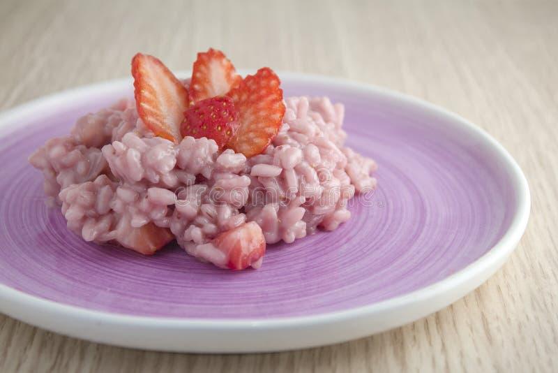 Rijst met aardbeien op purpere plaat royalty-vrije stock fotografie