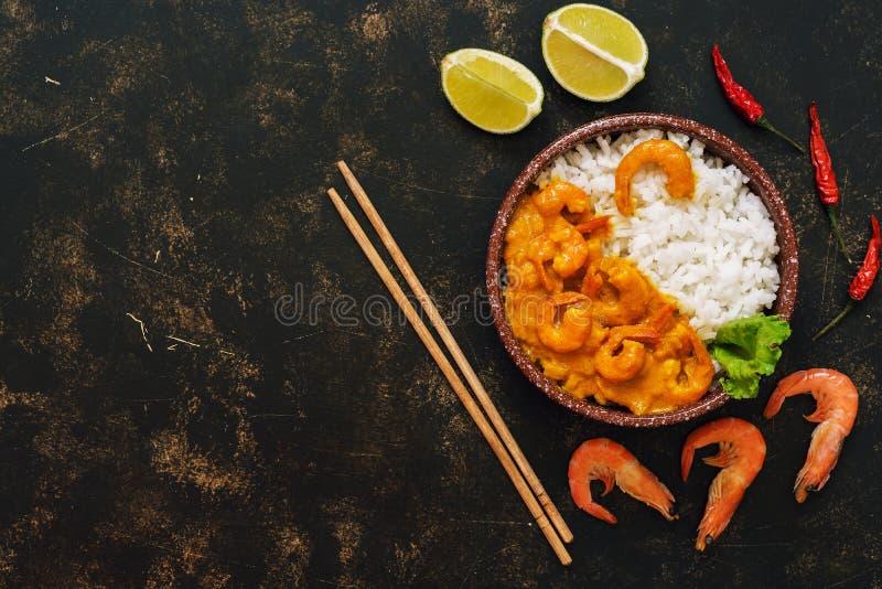 Rijst met garnalen in kerriesaus op een donkere rustieke achtergrond Het concept Aziatisch voedsel Hoogste mening, exemplaarruimt royalty-vrije stock foto