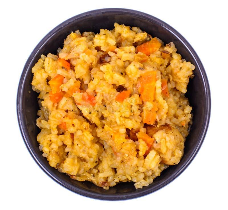 Rijst met groenten in zwarte kom op witte achtergrond Mening van hierboven stock afbeelding