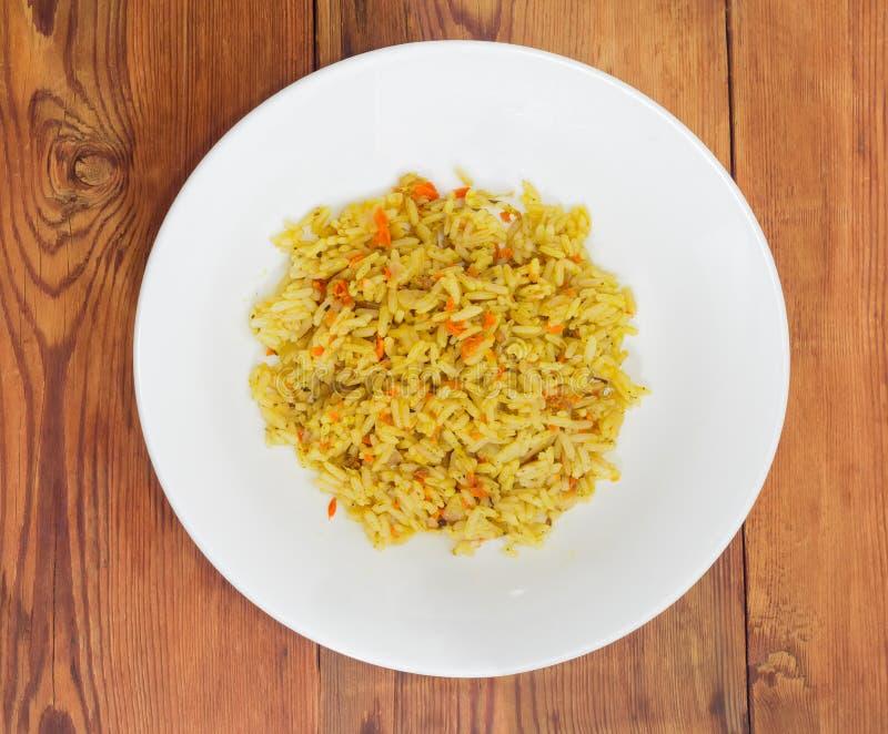 Rijst met wortelen en kruiden op witte schotel wordt gekookt die stock afbeeldingen