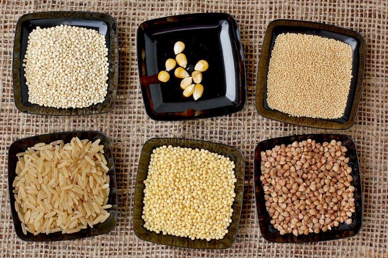 Rijst, quinoa, graan, gierst, boekweit, amarant in zwarte plaat op de jutedoek stock fotografie