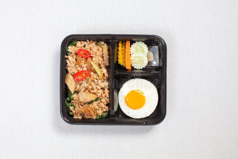 Rijst vermengd met basilicum en snakeskin gourami met gefrituurd ei, verpakt in een zwarte plastic doos, op een witte tafellade,  royalty-vrije stock fotografie