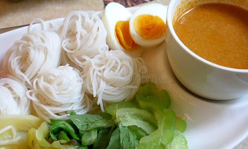 Rijstnoedels in de saus van de vissenkerrie met groenten Het heerlijke Thaise voedsel dienen met gekookt ei stock afbeeldingen