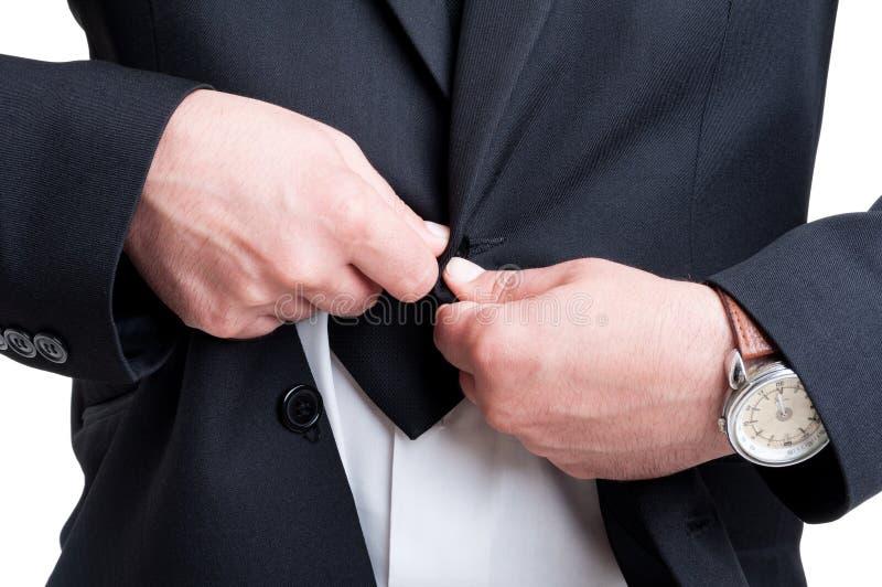Rik affärsman som knäppas eller knäpper upp dräktomslaget arkivfoton