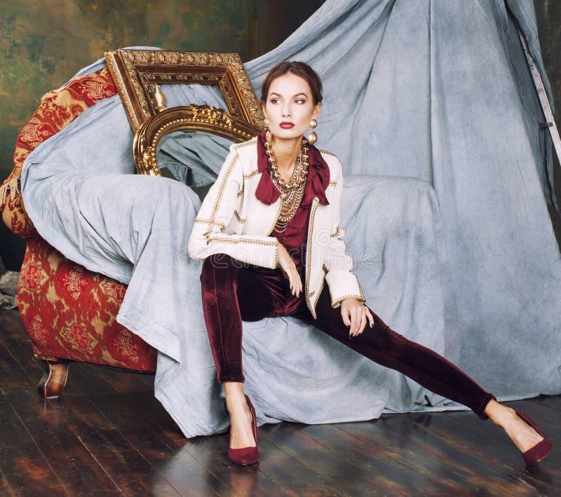 Rik brunettkvinna för skönhet i lyxigt inre near royaltyfri fotografi