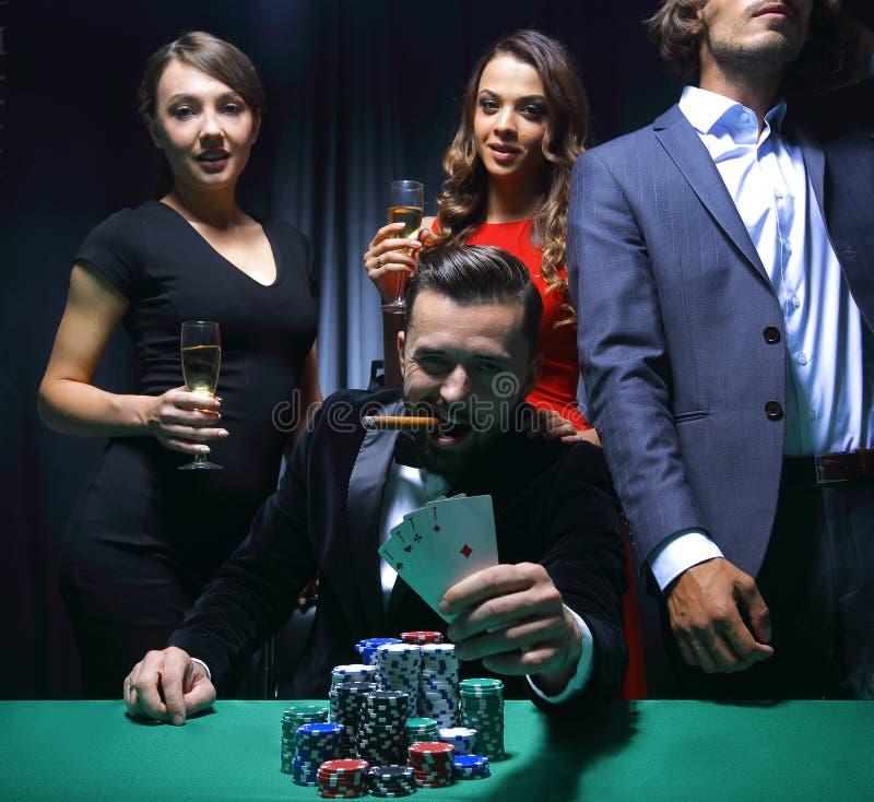 Rik stilig man som röker cigarren och spelar i kasinot royaltyfri bild
