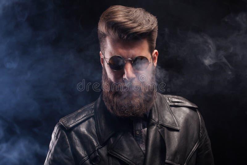 Rik stilig skäggig man med solglasögon och läderomslaget över svart bakgrund royaltyfria bilder