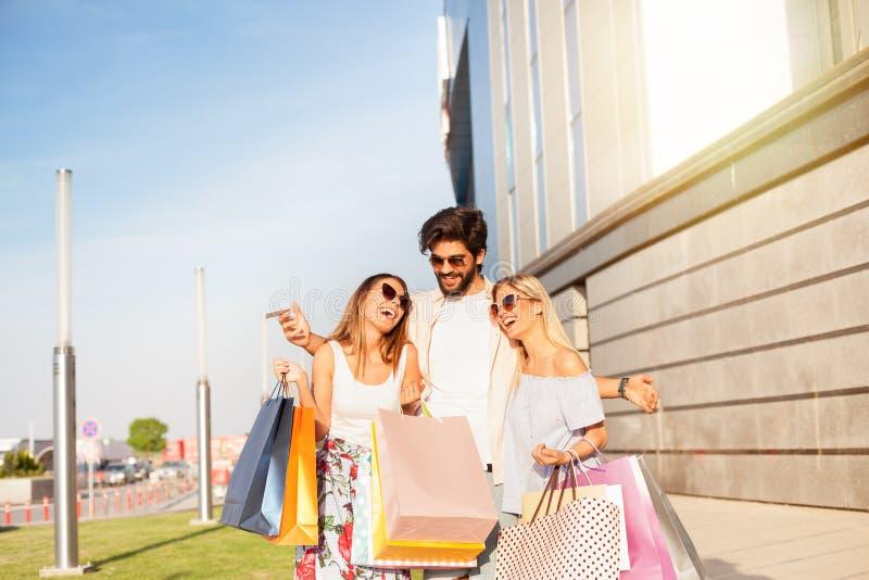 Rik ung man med två flickor i shopping fotografering för bildbyråer