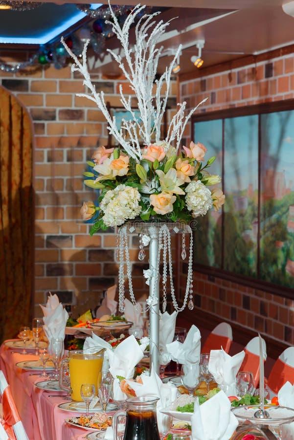 Rika bordsuppsatser som göras av rosa buketter på högväxta vaser, står fotografering för bildbyråer