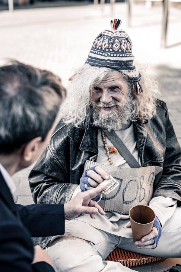 Rikeman som deltar i handling av välgörenhet, medan räcka pengar till hemlöns fotografering för bildbyråer