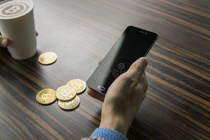 Rikeman som rymmer ett bitcoinmynt och dricker ett kaffe med en telefon, och guld- mynt av bitcoin på en tabell Vinst från fotografering för bildbyråer
