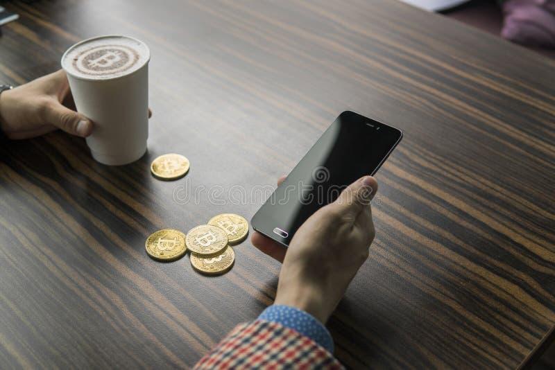 Rikeman som rymmer ett bitcoinmynt och dricker ett kaffe med en telefon, och guld- mynt av bitcoin på en tabell Vinst från arkivfoton