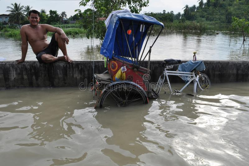 Riksza opuszcza na zalewającym moscie w Pathum Thani, Tajlandia, w Październiku 2011 fotografia royalty free