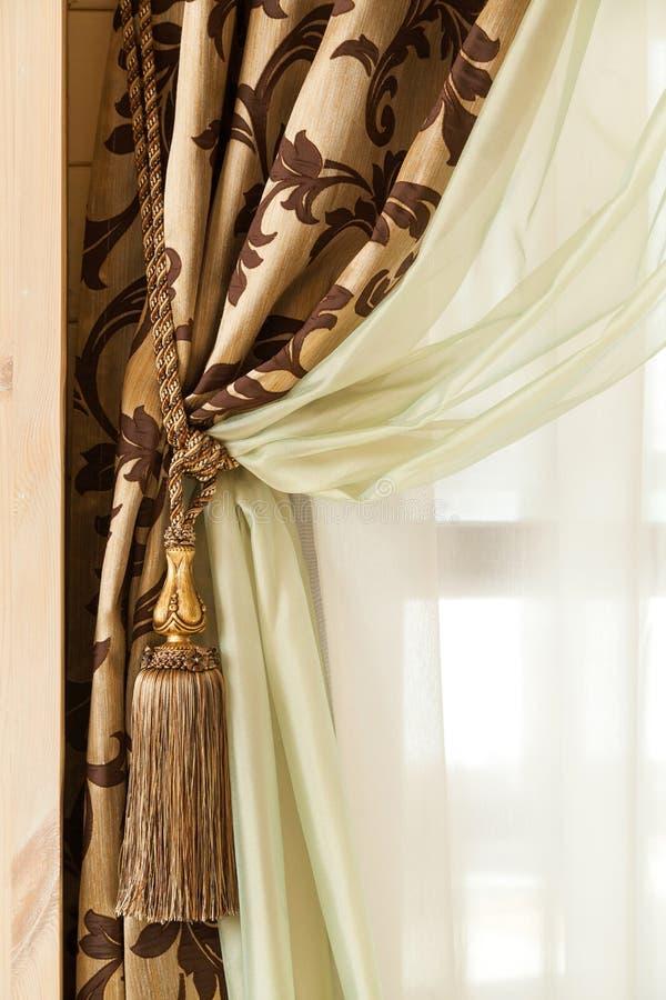 Rikt dekorerad gardin med en hållande rem arkivbild