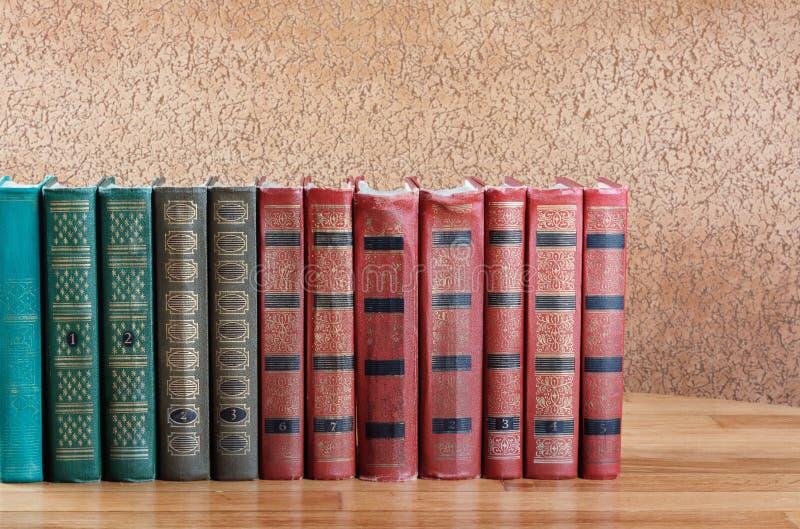 Rikt dekorerade volymer av böcker med en guld- bokstäver arkivfoton
