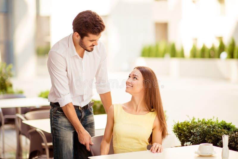 Riktig gentleman! Den unga stiliga brunettvännen justerar stolen av hans lyckliga dam, båda som kläs väl, på en solig terrass av  royaltyfri bild