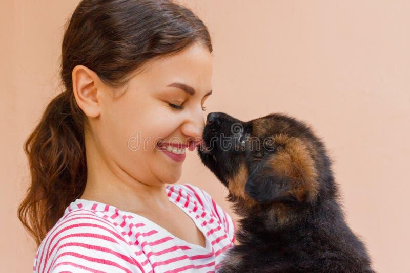 Riktigt kamratskap mellan flickan och valpen som ger en kyss royaltyfri bild