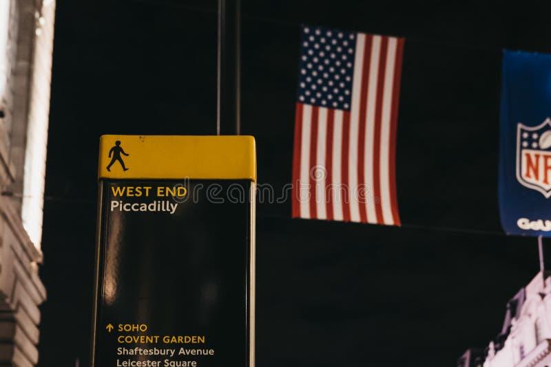Riktningen sjunger i Piccadilly Circus, London, UK-, USA och NFL-flaggor på bakgrunden royaltyfria bilder