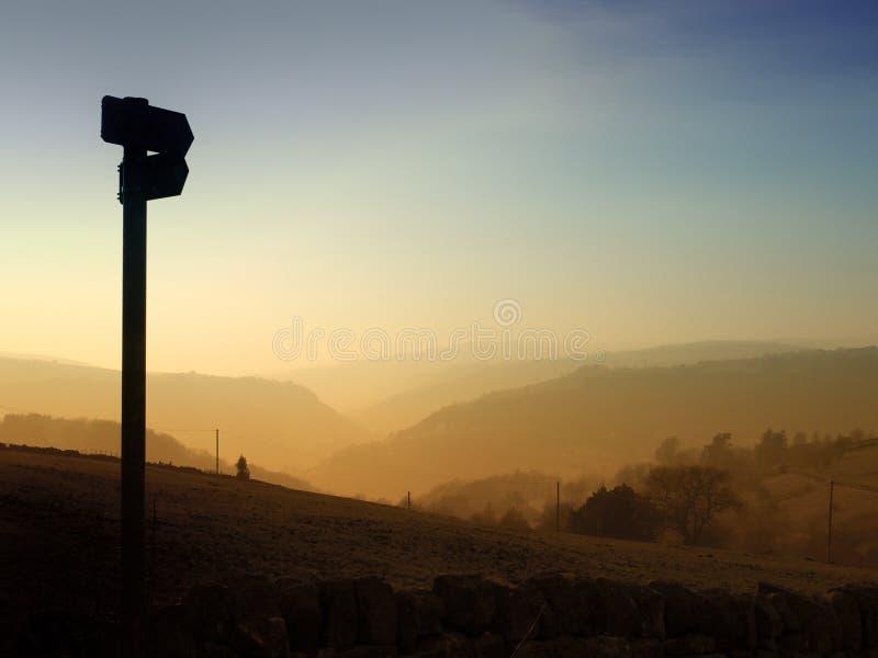 Riktningen undertecknar i konturn som pekar ner en glödande aftonsolnedgångdal med det guld- trädet, täckte kullar på skymning royaltyfri bild