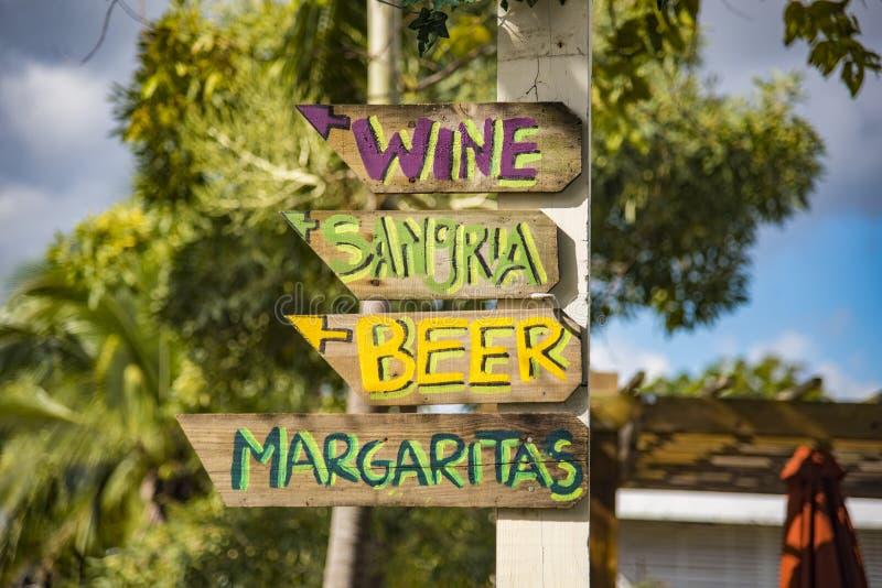 Riktningsstrandtecken som pekar till vin, sangria, öl och Marg royaltyfri foto